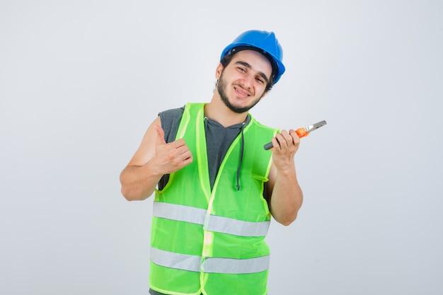 Junger baumeistermann in der arbeitskleidunguniform, die zangen hält, während daumen oben zeigt und fröhlich, vorderansicht schaut.