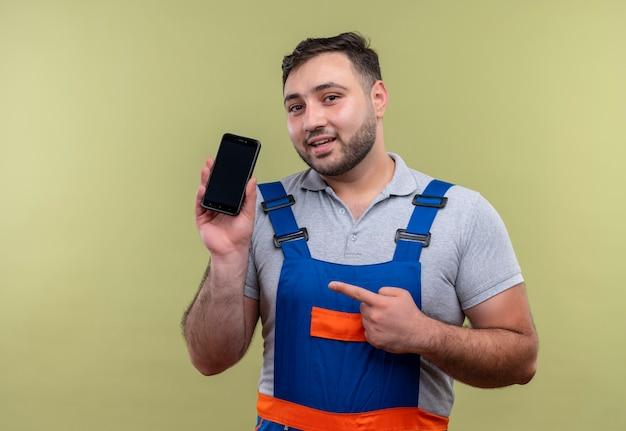 Junger baumeistermann in der bauuniform, die das smartphone zeigt, das mit dem finger auf es schaut, das sicheres lächeln über grünem hintergrund schaut