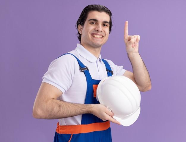 Junger baumeistermann in der bauuniform, die seinen sicherheitshelm hält, der vorne mit dem sicheren ausdruck zeigt, der mit dem zeigefinger oben zeigt, der über lila wand lächelnd steht