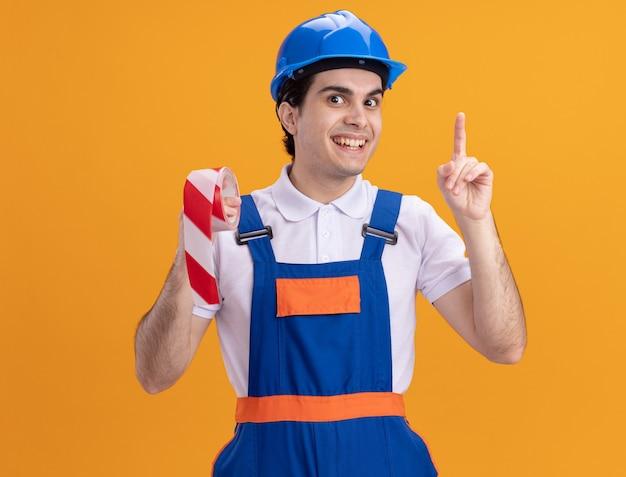 Junger baumeistermann in der bauuniform und im sicherheitshelm, der das warnband hält, das vorne glücklich und überrascht zeigt zeigefinger, der neue idee hat, die über orange wand steht