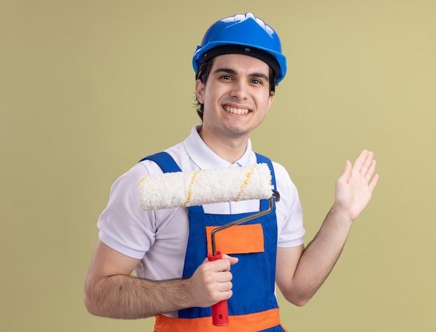 Junger baumeistermann in der bauuniform und im sicherheitshelm, der farbroller-lookign an der vorderseite hält, die mit hand über grüner wand winkend winken