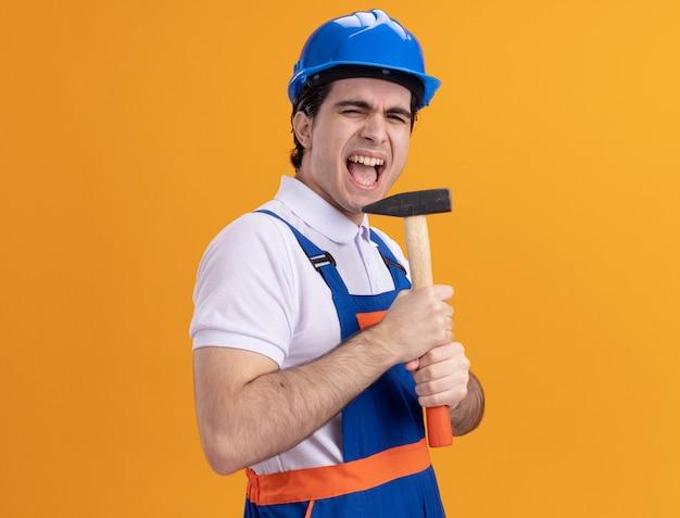 Junger baumeistermann in der bauuniform und im sicherheitshelm, der hammer hält, der als ein mikrofon verwendet, das emotionales und glückliches stehen über orange wand singt