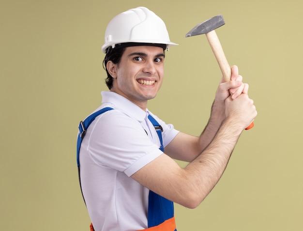 Junger baumeistermann in der bauuniform und im sicherheitshelm, der hammer hält, der vorne lächelnd schlau über grüne wand steht