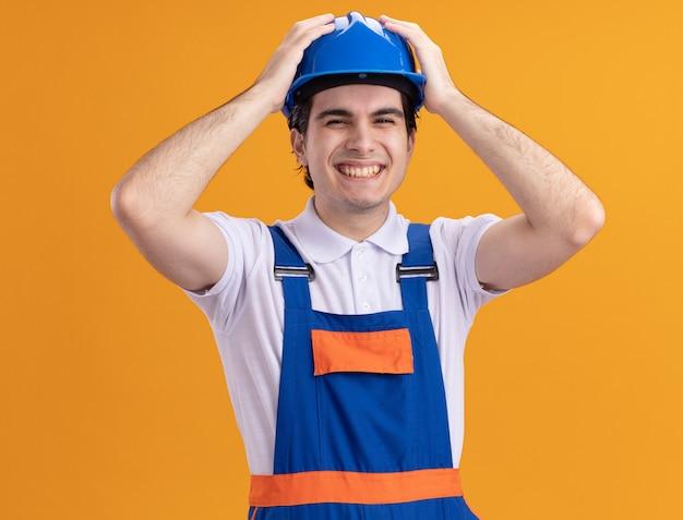 Junger baumeistermann in der bauuniform und im sicherheitshelm, der hammer hält, schaut vorne glücklich und aufgeregt mit händen auf seinem kopf, der über orange wand steht
