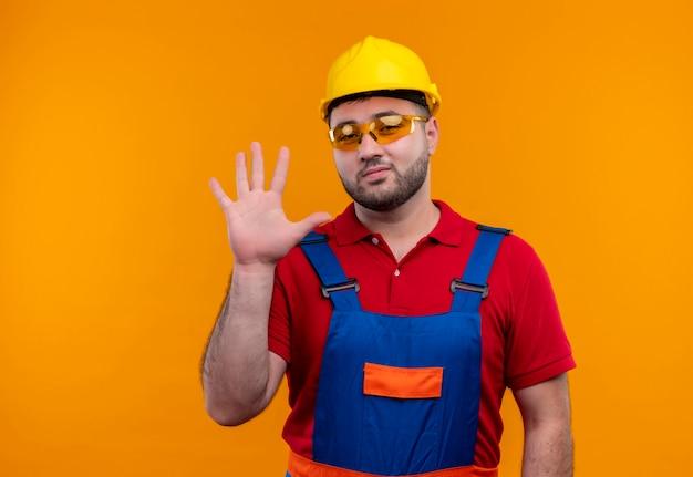 Junger baumeistermann in der bauuniform und im sicherheitshelm, der kamera betrachtet, die mit lächelnder hand winkt