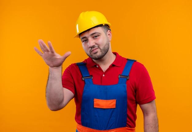 Junger baumeistermann in der bauuniform und im sicherheitshelm, der kamera mit skeptischem ausdruck betrachtet, der hand hebt, beruhigt geste