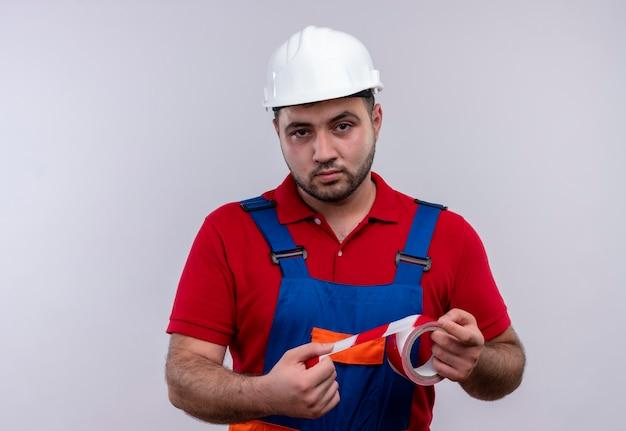 Junger baumeistermann in der bauuniform und im sicherheitshelm, der klebeband hält kamera an mit ernstem gesicht betrachtet