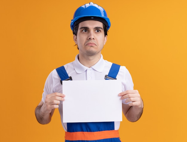 Junger baumeistermann in der bauuniform und im sicherheitshelm, der leere seite hält, die mit traurigem ausdruck auf gesicht steht, das über orange wand steht