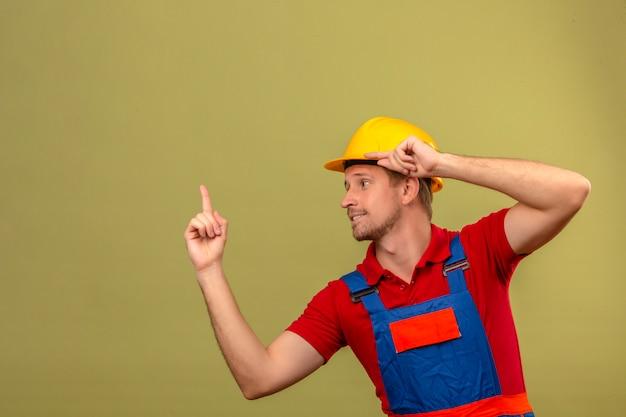 Junger baumeistermann in der bauuniform und im sicherheitshelm, der oben zeigt und seitlich mit sicherem blick über isolierte grüne wand mit kopienraum schaut