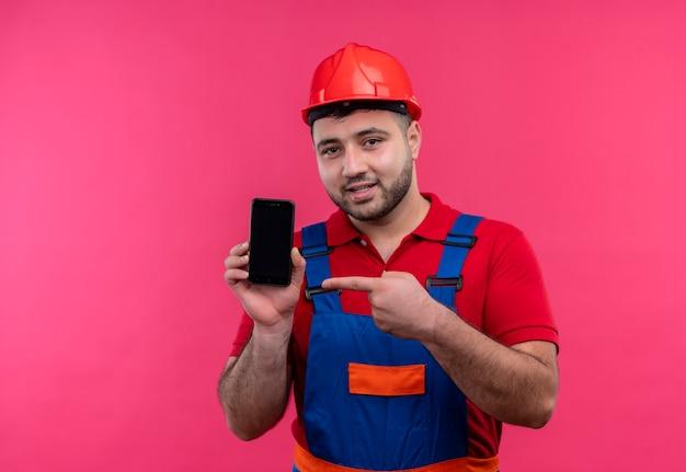 Junger baumeistermann in der bauuniform und im sicherheitshelm, der smartphone hält, das mit finger zum int lächeln zeigt