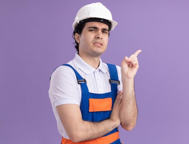 Junger baumeistermann in der bauuniform und im sicherheitshelm, der verwirrt zeigt und mit dem zeigefinger auf die seite zeigt, die über lila wand steht