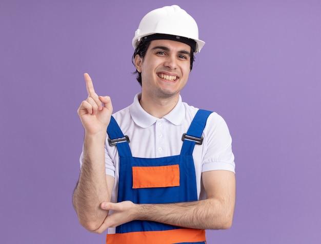 Junger baumeistermann in der bauuniform und im sicherheitshelm, der vorne lächelnd zeigt und mit dem zeigefinger auf die seite zeigt, die über lila wand steht