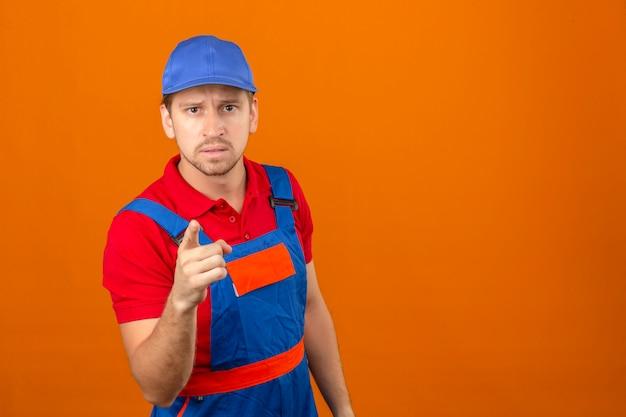 Junger baumeistermann in der bauuniform und im sicherheitshelm, der zeigefinger zur kamera und zum ausdruck zeigt, als frage über isolierte orange wand mit kopienraum