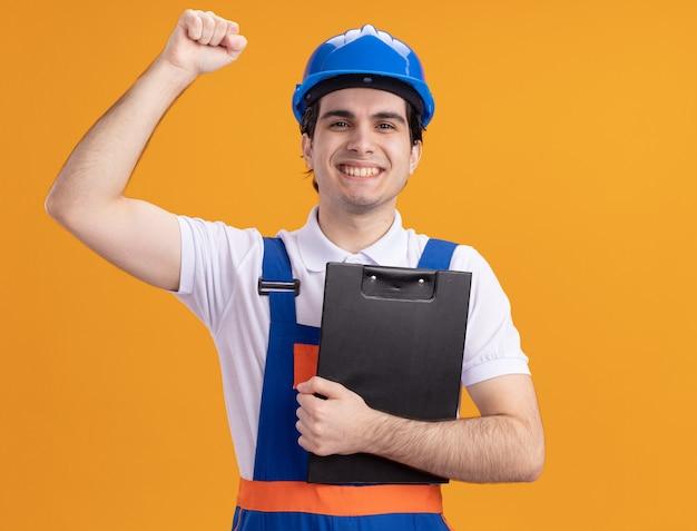 Junger baumeistermann in der bauuniform und im sicherheitshelm, der zwischenablage hält, die front glücklich und positiv anhebende faust steht, die über orange wand steht