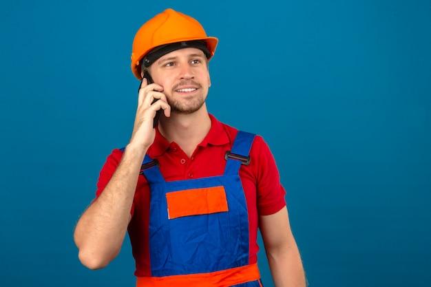 Junger baumeistermann in der bauuniform und im sicherheitshelm, die auf handy mit glücklichem gesicht sprechen, das über blaue isolierte wand lächelt