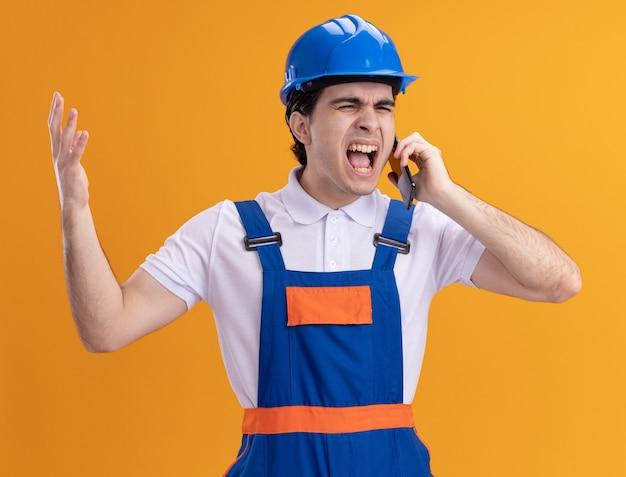 Junger baumeistermann in der bauuniform und im sicherheitshelm, die auf handy sprechen, das mit aggressivem ausdruck wütend und verrückt verrückt steht, der über orange wand steht
