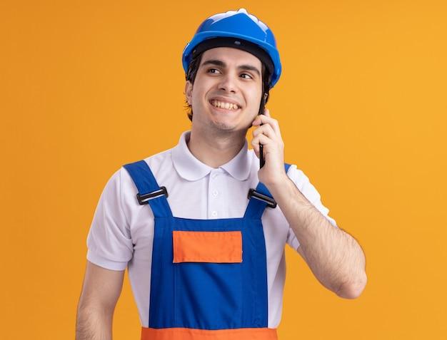 Junger baumeistermann in der bauuniform und im sicherheitshelm, die beiseite schauen mit lächeln auf gesicht sprechen auf handy, das über orange wand steht