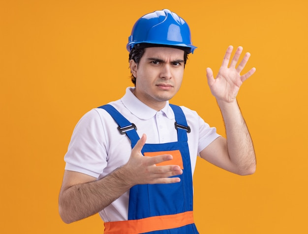 Junger baumeistermann in der bauuniform und im sicherheitshelm, die front betrachten, missfallen mit armen, die über orange wand stehen