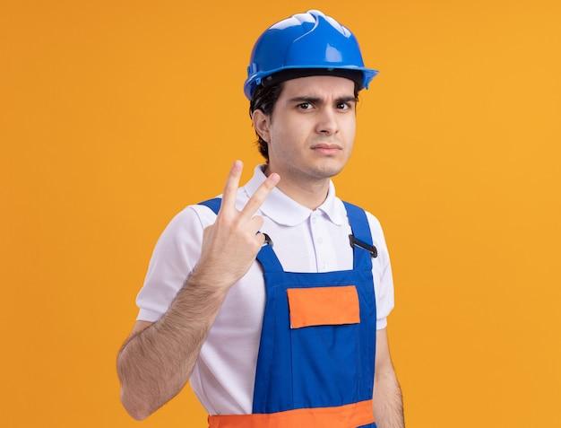 Junger baumeistermann in der bauuniform und im sicherheitshelm, die front mit ernstem gesicht betrachten, das nummer zwei zeigt, das über orange wand steht