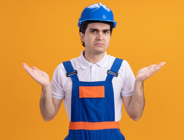 Junger baumeistermann in der bauuniform und im sicherheitshelm, die front verwirrt und unzufrieden mit erhobenen armen betrachten, die über orange wand stehen
