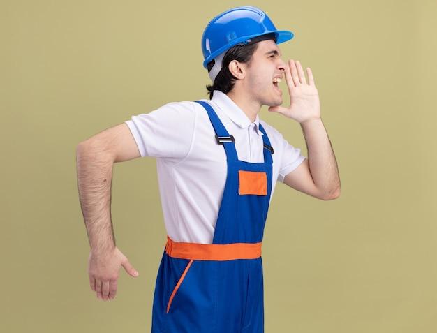 Junger baumeistermann in der bauuniform und im sicherheitshelm, die jemanden mit der hand nahe dem mund schreien oder rufen über grüner wand stehen