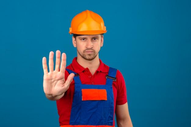 Junger baumeistermann in der bauuniform und im sicherheitshelm, die mit offener hand stehen und stoppschild mit ernsthafter und sicherer ausdrucksverteidigungsgeste über isolierter blauer wand tun