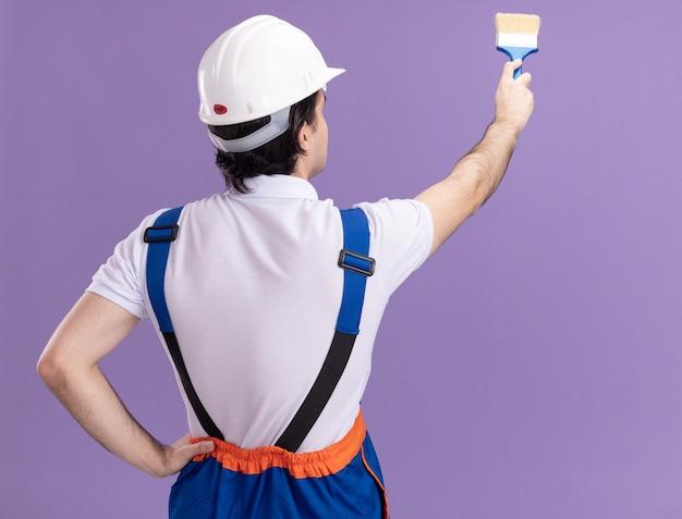 Junger baumeistermann in der bauuniform und im sicherheitshelm, die mit seiner hinteren farbwand mit farbroller über lila wand stehen