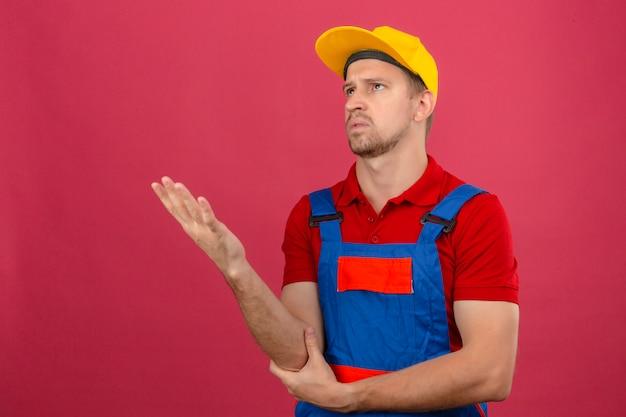 Junger baumeistermann in der bauuniform und im sicherheitshelm, die nach oben schauen und verwirrte geste mit hand und ausdruck machen, als frage über isolierte rosa wand stellen