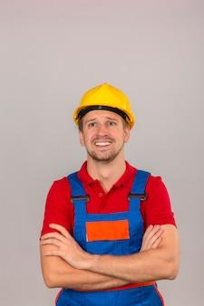 Junger baumeistermann in der bauuniform und im sicherheitshelm, die oben mit erschrockenem gesicht über isolierter weißer wand suchen