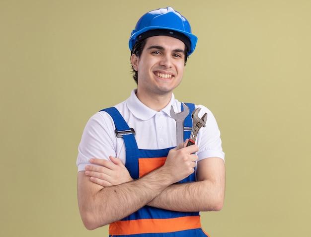 Junger baumeistermann in der bauuniform und im sicherheitshelm, die schraubenschlüssel halten, die vorne mit lächeln auf gesicht stehen, das über grüner wand steht