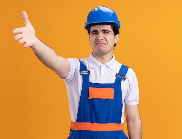 Junger baumeistermann in der bauuniform und im sicherheitshelm, die verwirrt betrachten hand in missfallen und empörung, die über orange wand stehen