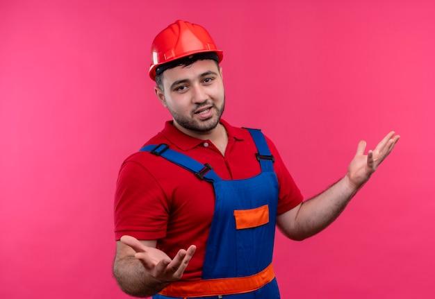 Junger baumeistermann in der bauuniform und im sicherheitshelm, die verwirrt und unsicheres achselzucken ohne antwort schauen