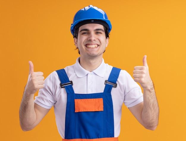 Junger baumeistermann in der bauuniform und im sicherheitshelm, die vorne lächelnd fröhlich zeigen, daumen hoch stehend über orange wand