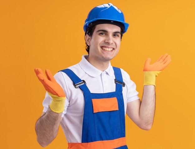 Junger baumeistermann in der bauuniform und im sicherheitshelm, die vorne lächelnd mit glücklichem gesicht stehen über orange wand schauen