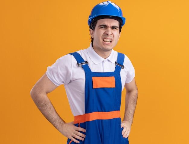 Junger baumeistermann in der bauuniform und im sicherheitshelm, die vorne mit dem verärgerten gesicht betrachten, das enttäuscht ist, über orange wand zu stehen