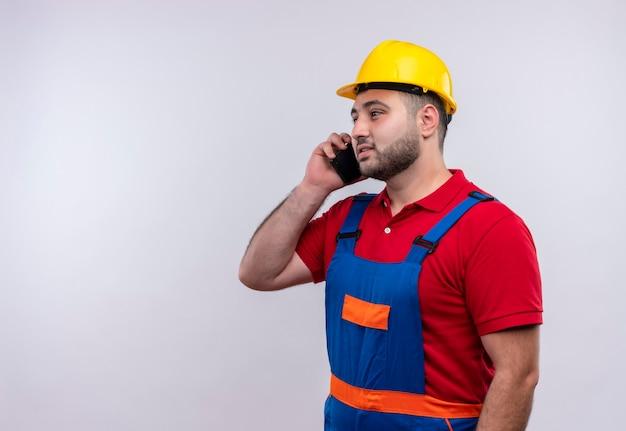 Junger baumeistermann in der bauuniform und im sicherheitshelm lächelnd, während auf mobiltelefon gesprochen