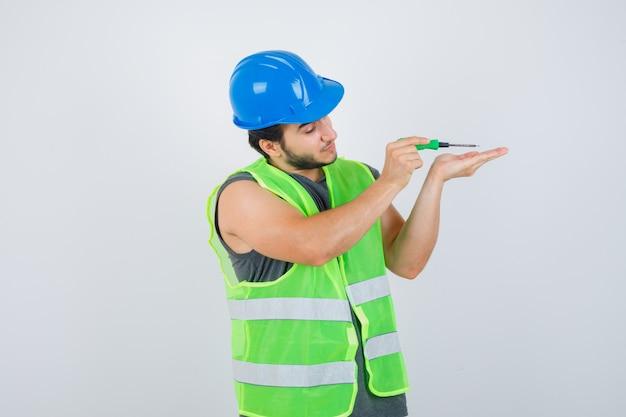 Junger baumeistermann in der uniform unter verwendung des schraubendrehers, während er arbeitet und fokussierte vorderansicht schaut.