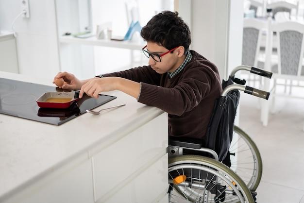 Junger behinderter junge, der frühstück in der küche macht