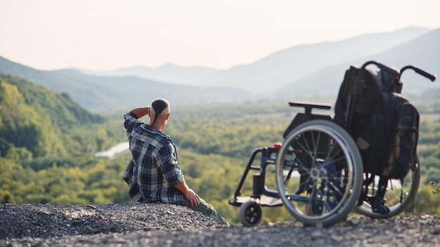 Junger behinderter mann, der auf dem berggipfel nahe rollstuhl sitzt und frische luft und naturschönheit genießt. das leben genießen.