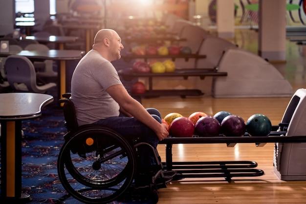 Junger behinderter mann im rollstuhl, der bowling im club spielt