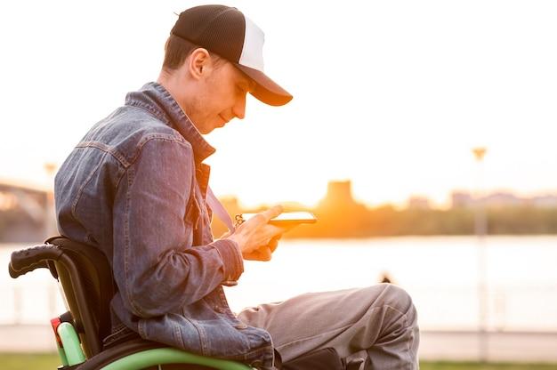 Junger behinderter mann im rollstuhl walking park hochwertiges foto