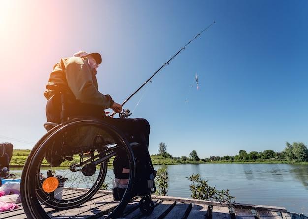 Junger behinderter mann im rollstuhlfischen