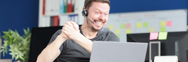 Junger behinderter mann in kopfhörern, der über ein laptop-online-dating-konzept kommuniziert