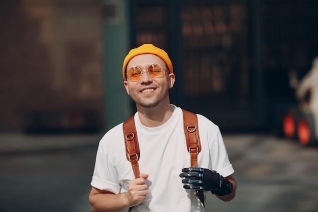 Junger behinderter mann mit künstlicher handprothese in freizeitkleidung und rucksack, der am sonnigen ...