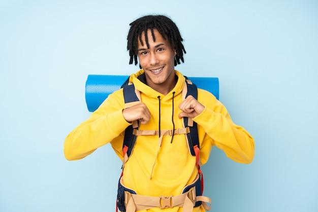 Junger bergsteiger-afroamerikanermann mit einem großen rucksack lokalisiert auf einem blauen stolzen und selbstzufriedenen