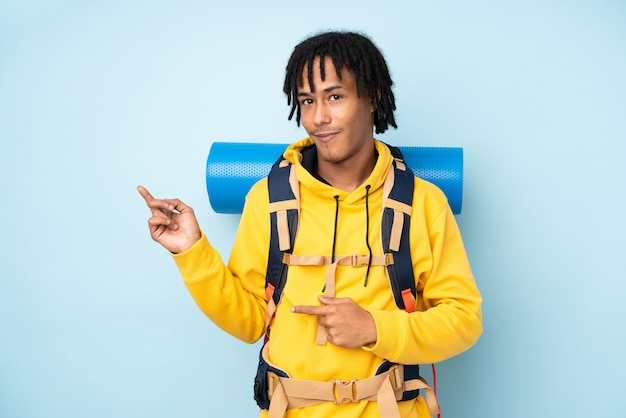 Junger bergsteiger-afroamerikanermann mit einem großen rucksack lokalisiert auf einem blauen zeigefinger zur seite