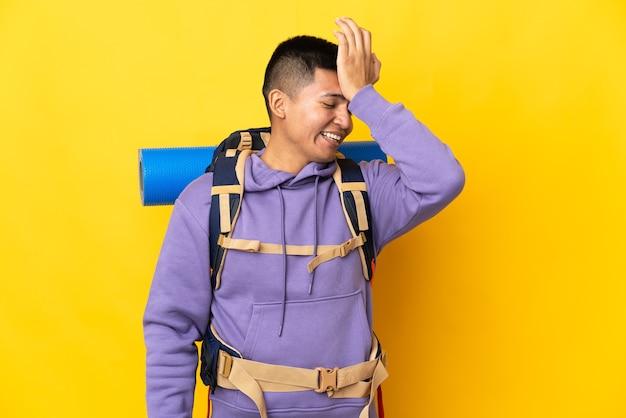 Junger bergsteiger mit einem großen rucksack, der auf gelber wand isoliert ist, hat etwas realisiert und beabsichtigt die lösung