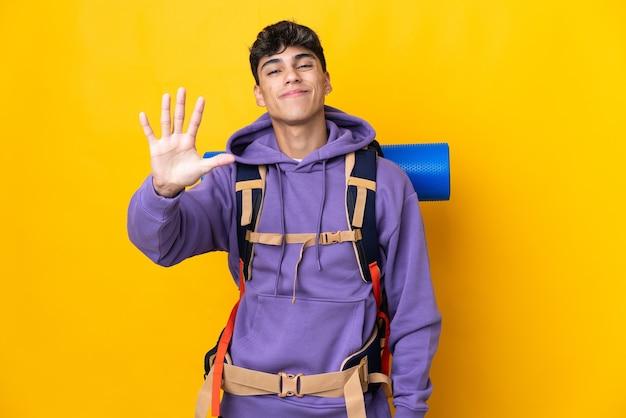 Junger bergsteigermann mit einem großen rucksack auf isoliertem gelb, das fünf mit den fingern zählt