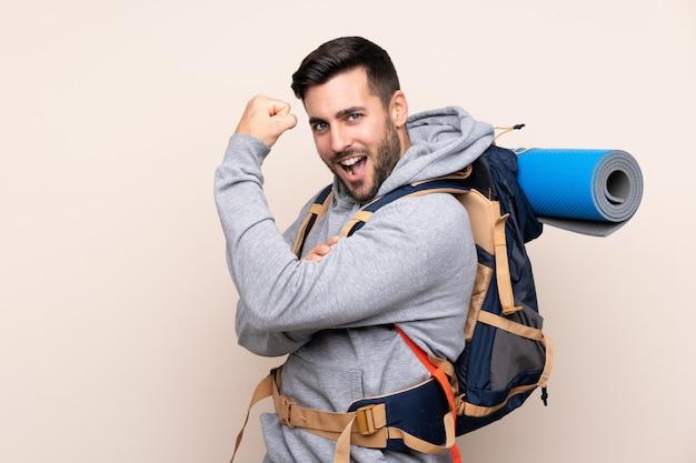 Junger bergsteigermann mit einem großen rucksack, der starke geste macht