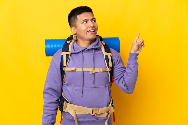 Junger bergsteigermann mit einem großen rucksack lokalisiert auf gelbem hintergrund, der beabsichtigt, die lösung zu verwirklichen, während ein finger anhebt